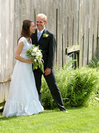 Bride and groom beside barn and ferns